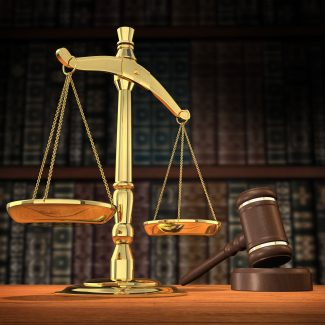 Scales of justice and gavel on desk with dark background that allows for copyspace.