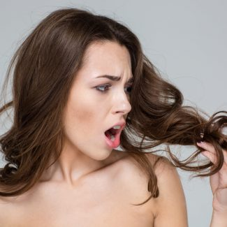 Disappointed  woman looking at her hair